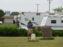 Field crew member Professor Holmgren (of Franklin and Marshall College, PA) documents a historic cemetery surrounded by a Type II camp just south of Tioga, ND in August 2012.