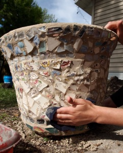 Molly is finalizing the mosaic grouting process on a reused terra-cotta potter.