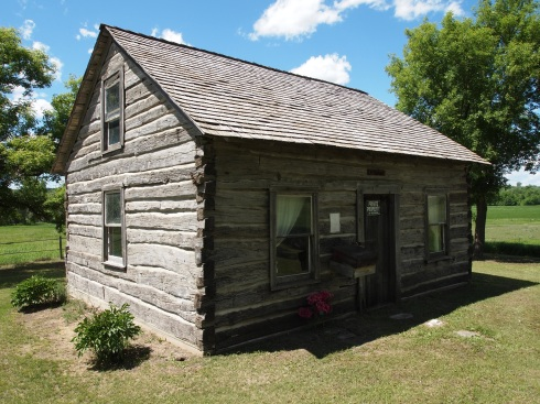 A June 16, 2013 photo of the Slattum Cabin. Note the gable end elevation, and compare the seams of the log cabin with the seams of the gable elevation in the 1950s photo. They are the same.