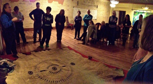 Dakota Goodhouse explains the stories reflected by and attached to the pictographs on the bison hide.