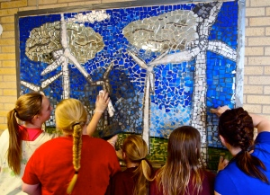 Teacher Mindi Paulson (far right) leads students in grouting the public wind turbine mosaic at the Langdon Elementary School.